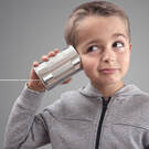 little boy with tin can and string held up to his ear like telephone