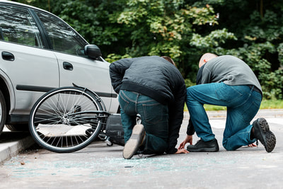 two men kneeling on road where bicycle and car have collided