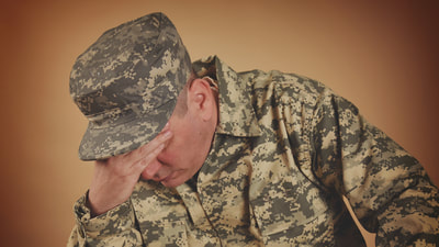 military man in fatigues who appears stressed or sad
